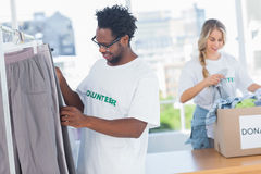 Volontärer som tar kläder ut ur en donationask Arkivfoton