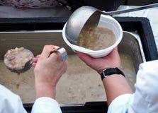 Volontärer tjänar som en varm soppa i en plast- maträtt för fattigt och hemlöst arkivbild