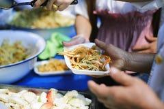 Volont?rer ger mat f?r tiggare: Begreppsmatning och hj?lp: Begrepp av mat som delar f?r att det fattigt ska l?tta hunger: arkivfoto
