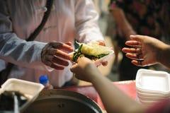 Volont?rer ger mat f?r tiggare: Begreppsmatning och hj?lp: Begrepp av mat som delar f?r att det fattigt ska l?tta hunger: arkivbilder