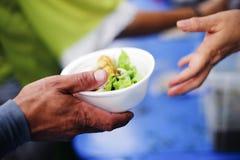 Volont?rer ger mat f?r tiggare: Begreppsmatning och hj?lp: Begrepp av mat som delar f?r att det fattigt ska l?tta hunger: arkivfoton