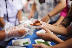 Volont?rer ger mat f?r tiggare: Begreppsmatning och hj?lp: Begrepp av mat som delar f?r att det fattigt ska l?tta hunger: fotografering för bildbyråer
