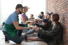 Volont?rer som ger mat till fattigt folk arkivfoto