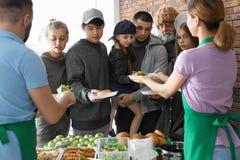 Volont?rer som ger mat till fattigt folk royaltyfri bild
