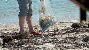 Volontaire écologique rassemblant des déchets sur le bord de mer au sachet en plastique Concept de pollution environnementale et  clips vidéos