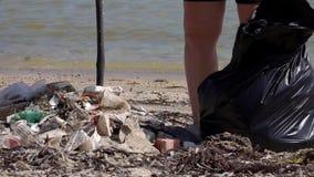 Volontaire écologique rassemblant des déchets sur le bord de mer au sachet en plastique Concept de pollution environnementale et  banque de vidéos