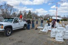 Volontaire d'étudiants pour aider une victime d'inondation Photos stock