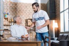 Volontaire de soin donnant un verre de l'eau à un retraité malade Image stock