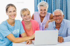 Volontaire et aînés à l'aide d'un ordinateur portable Images libres de droits
