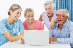 Volontaire et aînés à l'aide d'un ordinateur portable Photographie stock libre de droits