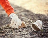 Volontaire prenant des ordures du sable image libre de droits