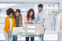 Volontaires à l'aide d'un ordinateur portable et prenant des vêtements de boîte de donations Images stock