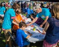 Volontaires aidant la couleur d'enfants photo stock