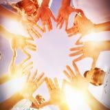 Volontaires avec des mains ensemble contre le ciel bleu Photographie stock