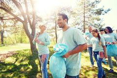 Volontaires avec des sacs de déchets marchant dehors photographie stock libre de droits