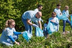 Volontaires avec des sacs de déchets nettoyant le secteur de parc Image libre de droits