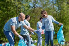 Volontaires avec des sacs de déchets nettoyant le secteur de parc Photographie stock