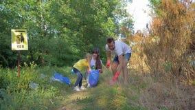Volontaires de famille, jeune mère et père avec soin de fille d'enfant au sujet de nature d'écologie et rassembler les déchets en banque de vidéos