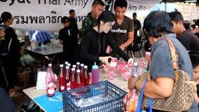 Volontaires donnant les boissons gratuites aux personnes en deuil au palais grand à Bangkok Photos libres de droits