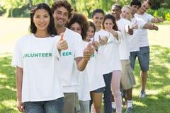 Volontaires faisant des gestes des pouces en parc Photos libres de droits