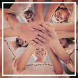 Volontaires heureux avec des mains ensemble contre le ciel bleu Image stock