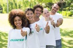 Volontaires sûrs faisant des gestes des pouces  Photo libre de droits