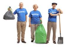 Volontaires supérieurs avec des sacs de rebut et une pelle image stock