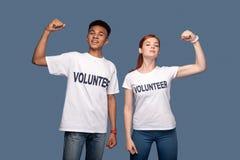 Volontari allegri positivi che tengono le loro mani su Fotografia Stock Libera da Diritti