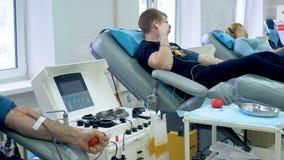 Volontari che donano sangue in un centro moderno, macchina medica nel lavoro stock footage