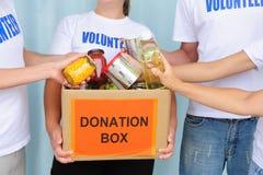 Volontari che mettono alimento in casella di donazione fotografia stock