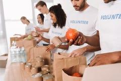 Volontari che mettono alimento e le bevande nelle borse fotografia stock libera da diritti