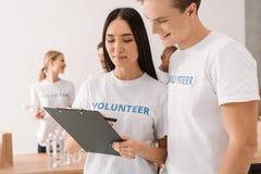 Volontari con la lavagna per appunti che fa lavoro di ufficio Immagini Stock Libere da Diritti