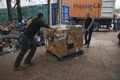 Volontari dalla spinta BRITANNICA di BookCycle un pallet dei libri fotografie stock libere da diritti