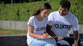 Volontari positivi dell'internazionale che si siedono nel parco stock footage
