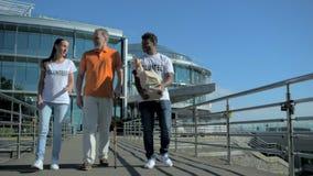 Volontari utili positivi che camminano con un uomo senior stock footage