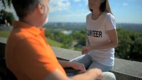 Volontario allegro che ha una conversazione con un uomo wheelchaired archivi video