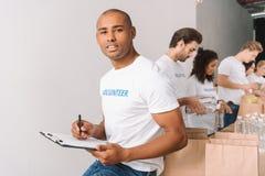 Volontario dell'afroamericano con la lavagna per appunti Immagine Stock