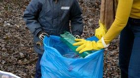 Volontario della donna con il suo bambino che pulisce i rifiuti dal fiume Concetto dell'ambiente e di ecologia archivi video