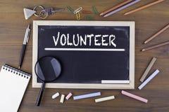 volontario Testo sul bordo di gesso Tavola di legno con una lente d'ingrandimento e gli utensili di scrittura fotografie stock