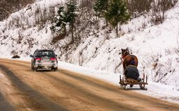 Traffic in mountainous rural area in winter. Volovets, Ukraine - December 16, 2016: traffic in mountainous rural area in winter. cart with one horse outscored by Stock Images