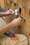 Volt Meter and Outlet. Electrician using a volt meter to test an exterior outlet stock photography