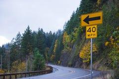 Volta da estrada bonita do outono com as setas do sinal de tráfego Fotografia de Stock