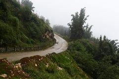 Volta da estrada da montanha Tempo chuvoso molhado nevoento imagens de stock royalty free