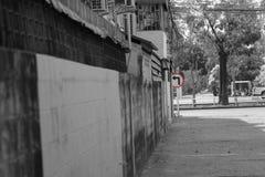 A volta retro deixada o tráfego assina na cor brilhante na aleia pequena da rua do fundo preto e branco na área urbana da cidade fotos de stock