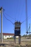 Voltage power transformer substation at village near farmhouse. Royalty Free Stock Photography