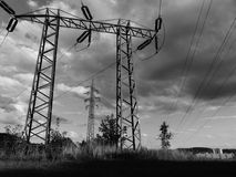 Voltage pylons in field.  Royalty Free Stock Images