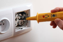 Voltage in socket. Checking voltage with detector in power socket stock photography