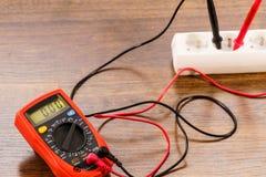 Voltaje de la medida en zócalo eléctrico con el multímetro fotografía de archivo