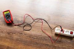 Voltaje de la medida en zócalo eléctrico con el multímetro fotos de archivo libres de regalías