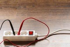Voltaje de la medida en zócalo eléctrico con el multímetro fotografía de archivo libre de regalías